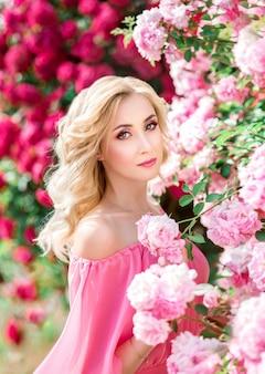 Belo retrato de uma mulher loira de rosas cor de rosa. maquiagem, cílios estendidos
