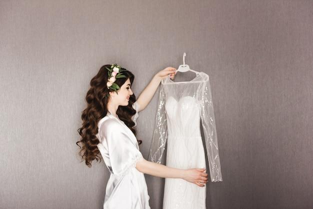 Belo retrato de uma noiva em um vestido com cachos de cabelo, colocando o vestido