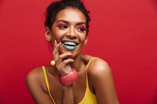 Belo retrato do modelo feminino americano africano feliz na camisa amarela, sorrindo e posando na câmera, isolada sobre parede vermelha
