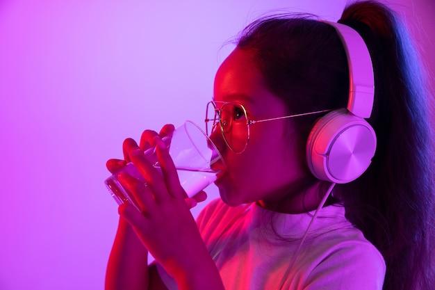 Belo retrato feminino de meio comprimento isolado em backgroud roxo em luz de néon. jovem adolescente emocional em óculos. emoções humanas, saúde, conceito de expressão facial. beber água pura.
