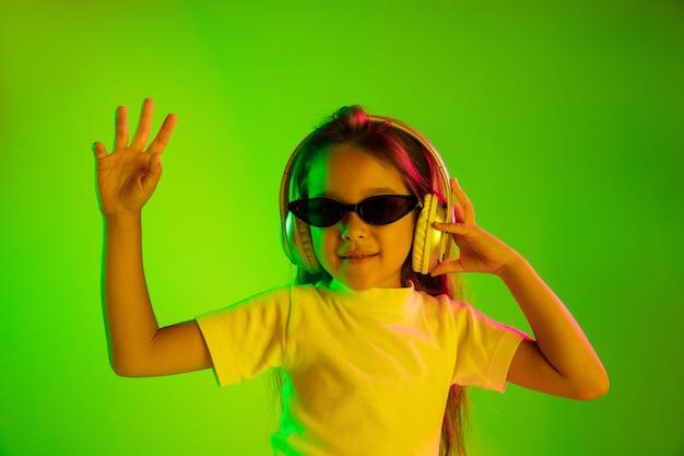 Belo retrato feminino de meio comprimento isolado em backgroud verde em luz de néon. jovem adolescente emocional em óculos de sol. emoções humanas, conceito de expressão facial. cores da moda. dançando, sorrindo.