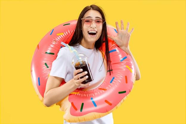 Belo retrato feminino de meio comprimento isolado na parede amarela. jovem mulher sorridente em óculos de sol vermelhos com bebida. expressão facial, verão, fim de semana, conceito de resort. cores da moda.