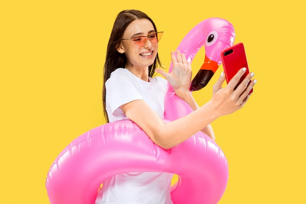Belo retrato feminino de meio comprimento isolado na parede amarela. jovem mulher sorridente em óculos de sol vermelhos, fazendo selfie. expressão facial, verão, fim de semana, conceito de resort. cores da moda.