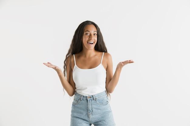 Belo retrato feminino de meio comprimento isolado na parede branca. jovem emocional afro-americana com cabelo comprido. expressão facial, conceito de emoções humanas. atônito, animado.