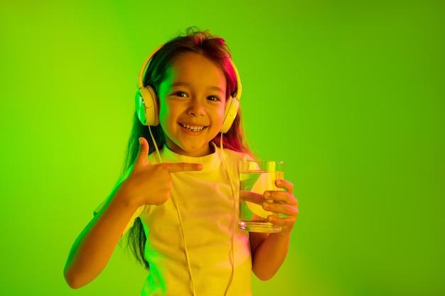Belo retrato feminino de meio comprimento isolado na parede verde em luz de néon. jovem adolescente emocional. emoções humanas, conceito de expressão facial. cores da moda. água potável e sorrindo.