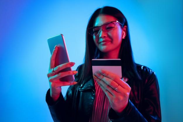 Belo retrato feminino de meio comprimento isolado no fundo azul do estúdio em luz de néon. mulher jovem e emocional. emoções humanas, conceito de expressão facial. usando smarptphone para contas de pagamentos online.