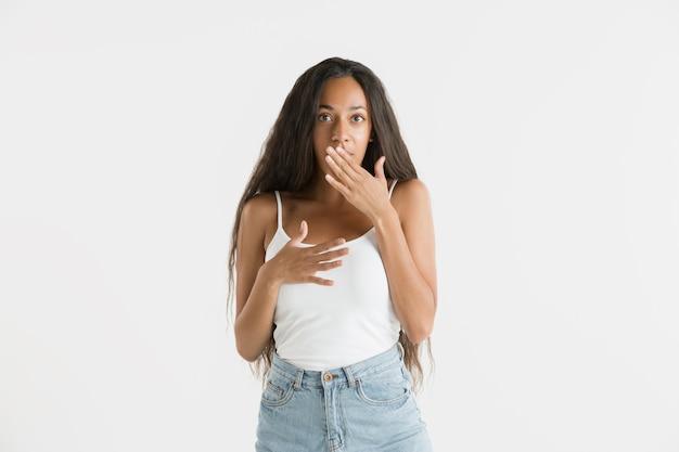 Belo retrato feminino de meio comprimento isolado no fundo branco do estúdio. jovem emocional afro-americana com cabelo comprido. expressão facial, conceito de emoções humanas. atônito, animado.