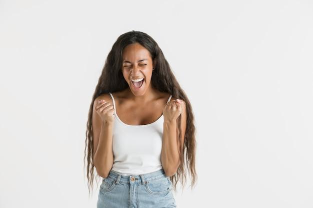Belo retrato feminino de meio comprimento isolado no fundo branco do estúdio. jovem emocional afro-americana com cabelo comprido. expressão facial, conceito de emoções humanas. comemorando e sorrindo.