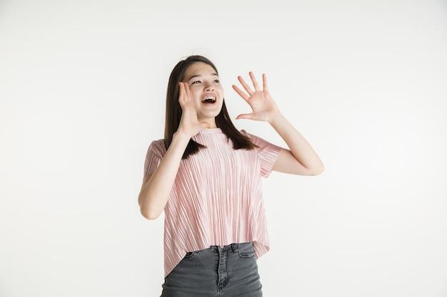 Belo retrato feminino de meio comprimento isolado no fundo branco do estúdio. jovem mulher emocional com roupas casuais. emoções humanas, conceito de expressão facial. espantado, admirado, ligando para vendas.