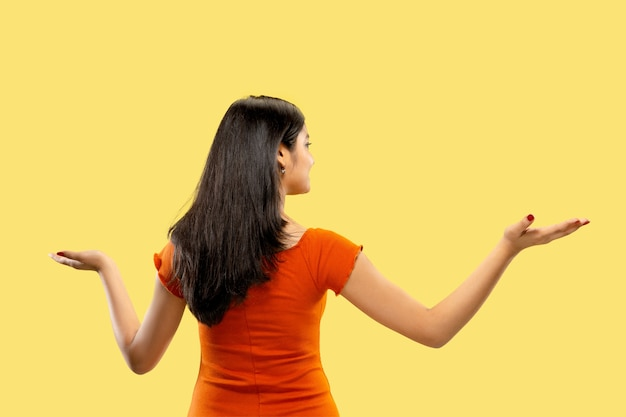 Belo retrato feminino de meio corpo isolado em amarelo