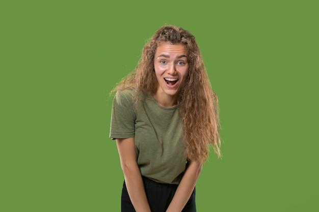 Belo retrato feminino metade frontal isolado no fundo verde do estúdio. jovem mulher surpresa emocional em pé com a boca aberta.