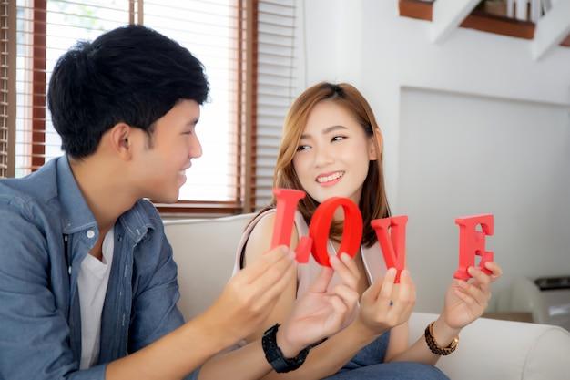 Belo retrato jovem casal asiático sentado no sofá, segurando a palavra amor juntos