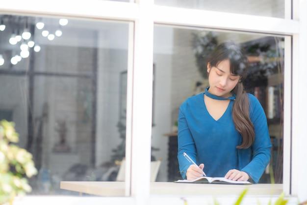 Belo retrato jovem mulher asiática escritor escrevendo no notebook