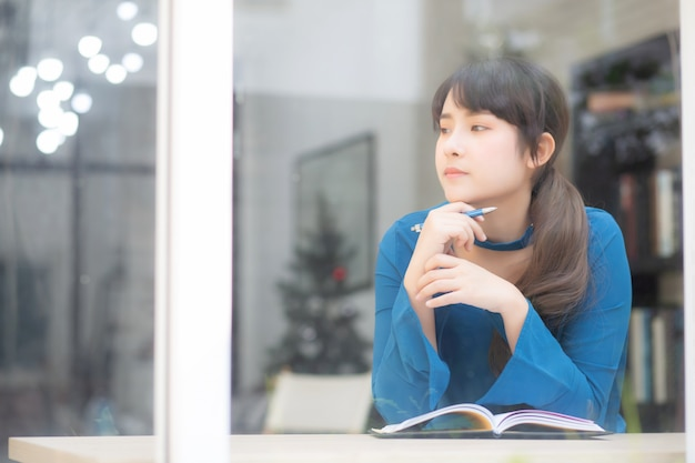 Belo retrato jovem mulher asiática escritor sorrindo pensando a ideia e escrevendo no notebook