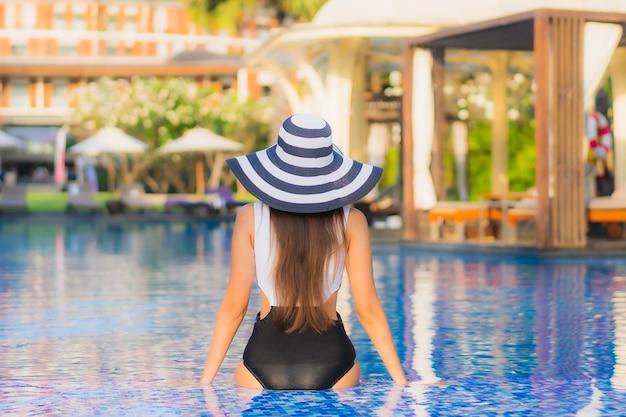 Belo retrato jovem mulher asiática sorriso feliz relaxar ao redor da piscina no hotel resort