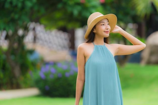 Belo retrato jovem mulher asiática sorriso feliz relaxar com um passeio no jardim