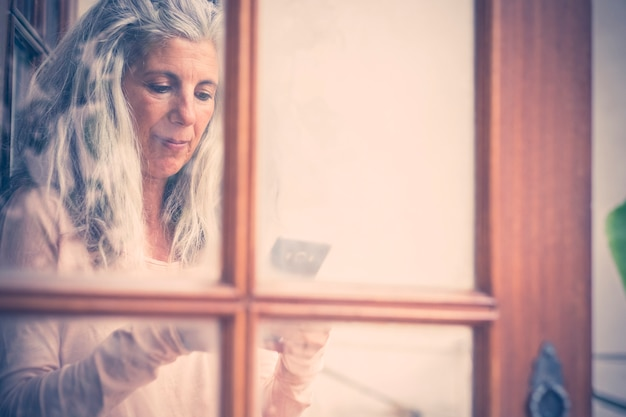 Belo retrato vintage antigo de uma mulher sênior alternativa digitando e lendo um telefone celular em casa, visto da janela