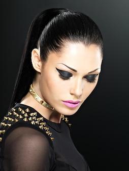 Belo rosto de moda mulher com maquiagem brilhante. garota sexy e elegante com pulseira de espinhos no pescoço