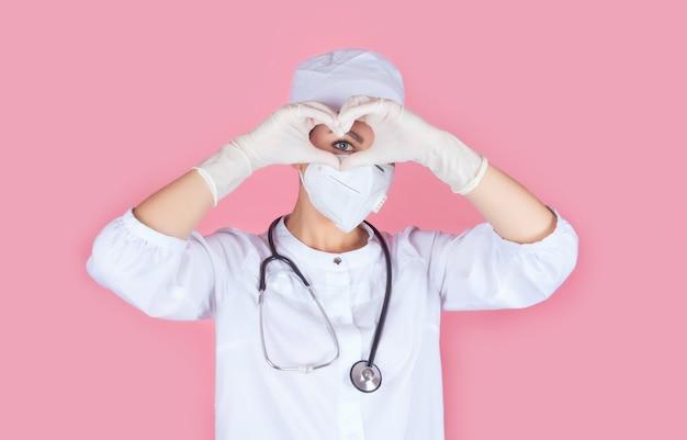 Belo rosto de um médico ou enfermeiro em um uniforme e máscara médica. as mãos em luvas esterilizadas têm a forma de um coração próximo ao olho. coração saudável