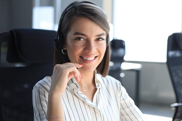Belo sorridente call center trabalhador em fones de ouvido está trabalhando em um escritório moderno.