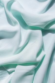 Belo tecido de seda de delicada cor água-marinha drapeado com pequenas dobras, fluindo suavemente,