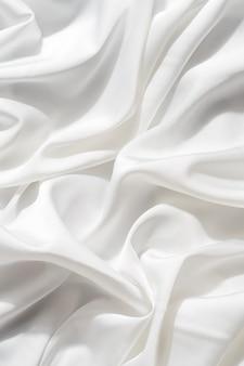 Belo tecido de seda de delicada cor branca drapeado com pequenas dobras, fluindo suavemente,