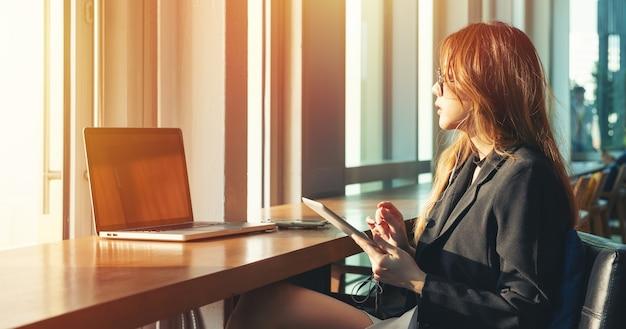 Belo terno preto de mulheres trabalhadoras vestir cabelo castanho comprido usar tablet e computador portátil em seu escritório. garota de negócios ues internet sem fio wi-fi do conceito de rede de coisas.