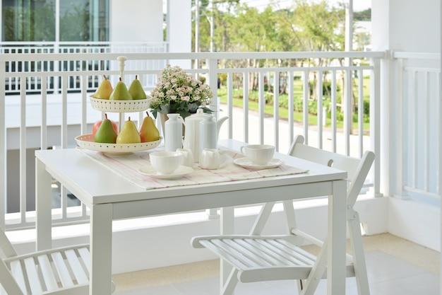 Belo terraço com móveis brancos e chá ou café em casa