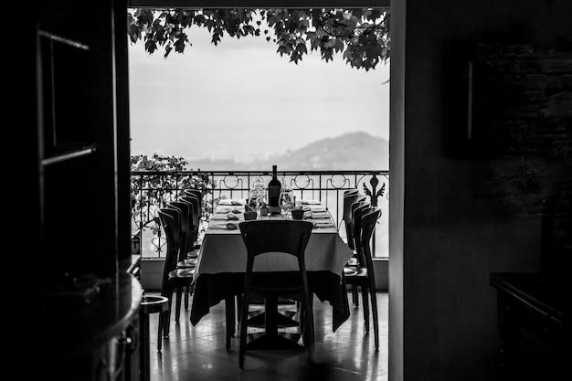 Belo terraço de um restaurante. pronto para a chegada de convidados. mesa servida. copos, pratos e vinho. preto e branco