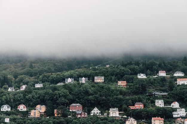 Belo tiro simétrico de casas coloridas em uma colina de nevoeiro