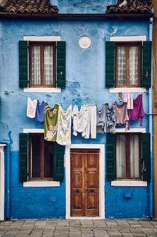 Belo tiro simétrico vertical de um prédio suburbano azul com roupas penduradas em uma corda