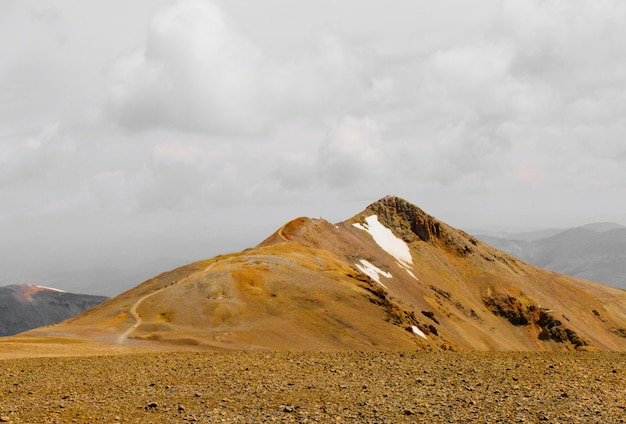 Belo tiro um campo com uma montanha à distância sob um céu nublado