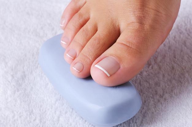 Belo único pé feminino com a bela pedicura nos dedos sobre uma fatia de sabonete azul.
