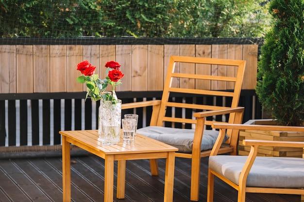 Belo vaso de rosa vermelha e bebida na mesa de madeira no telhado
