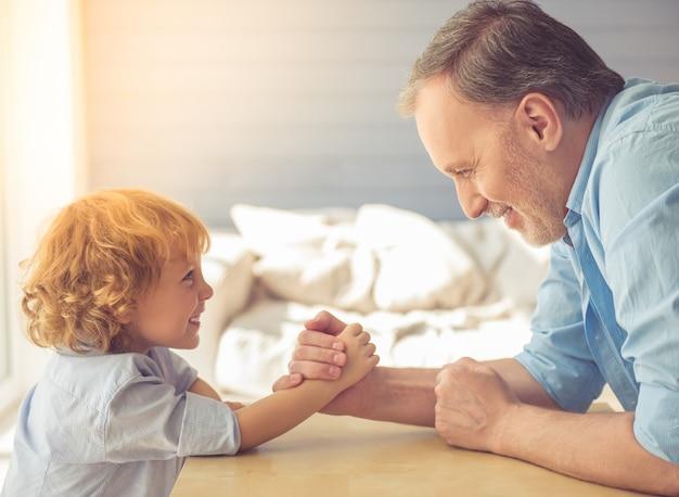 Belo vovô e neto estão lutando e sorrindo.