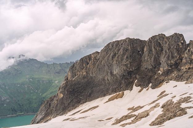 Belos alpes com lago, colina e neve na montanha rochosa