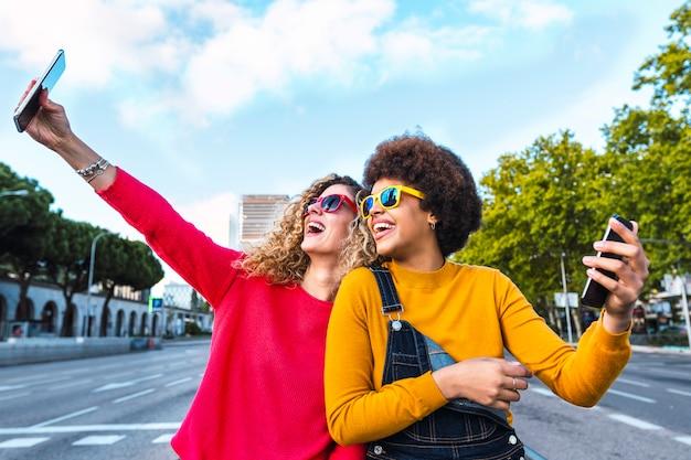 Belos amigos tomando uma selfie na rua. conceito de comunicação