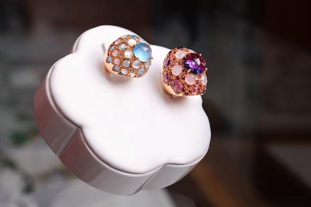 Belos anéis de ouro com pedras preciosas no carrinho de exposição branco. janela de loja de jóias de luxo. ametistas, safiras e diamantes azuis