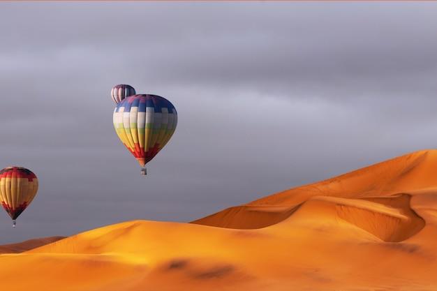 Belos balões coloridos de ar quente e nuvens dramáticas sobre as dunas de areia no deserto do namibe