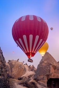 Belos balões de ar quente sobrevoando a paisagem da capadócia ao nascer do sol
