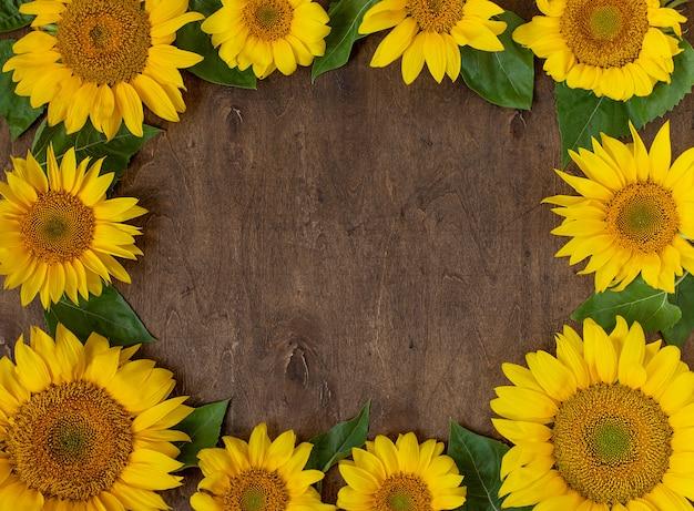 Belos girassóis amarelos sobre um fundo escuro de madeira