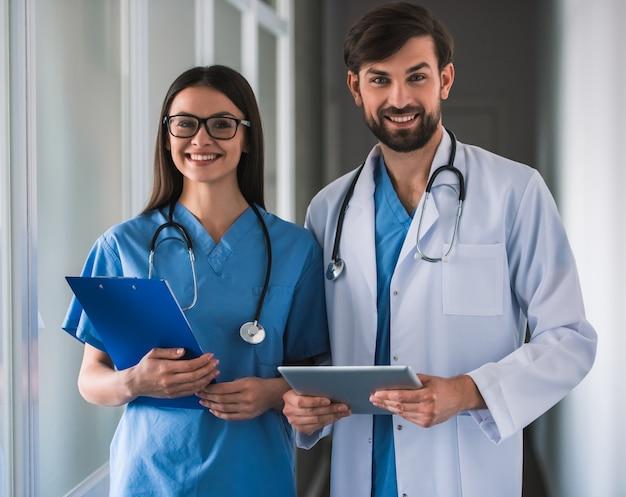Belos jovens médicos estão olhando para a câmera.