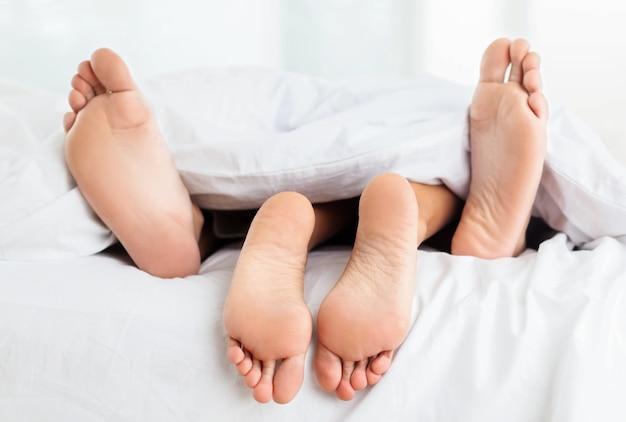 Belos pés de um jovem casal deitado na cama perto.