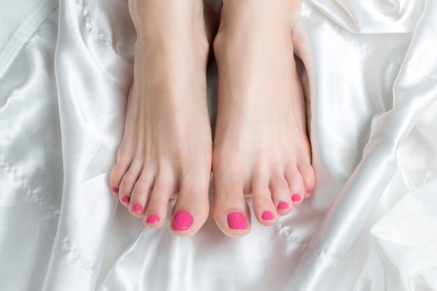 Belos pés femininos com unhas cor de rosa. pernas saudáveis.