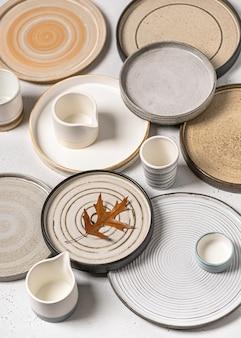 Belos talheres feitos à mão, pratos de cerâmica artesanais vazios e copos com folha de bordo em branco