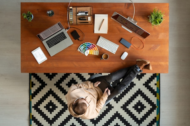 Bem acima da visão de um jovem com os pés na mesa e usando o bloco de desenho enquanto trabalha com design gráfico