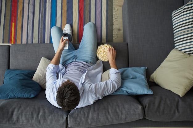 Bem acima da vista de um homem maduro assistindo tv e segurando uma tigela de pipoca enquanto está sentado no sofá em casa