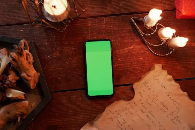 Bem acima da visualização do smartphone com tela verde queimando velas e carta na mesa de madeira