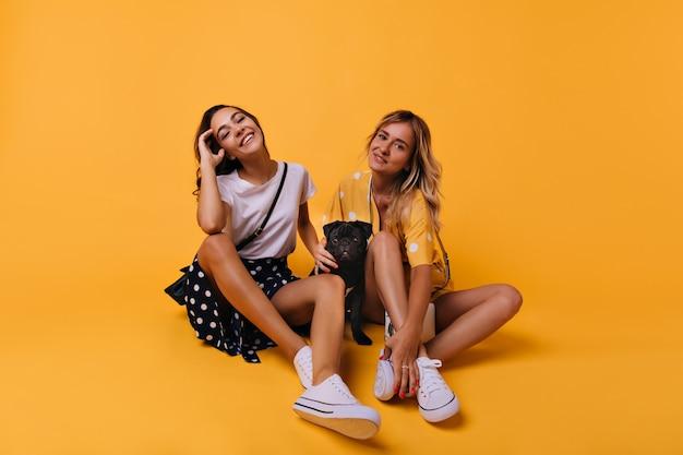 Bem-aventuradas irmãs brancas sentadas em amarelo com cachorro. retrato de modelos femininos relaxados, brincando com o cachorro.
