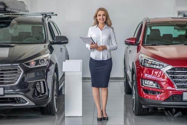 Bem estar. mulher adulta jovem sorridente com blusa branca e saia escura com documentos perto de carros no showroom